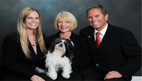 Three adults posing for a family photo with their dog.