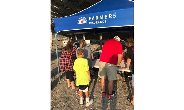 Four people hover over a table at a Farmers® booth