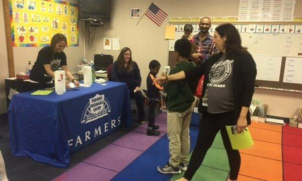 Children and parents laughing in a classroom with a Farmers Insurance promotional table in it