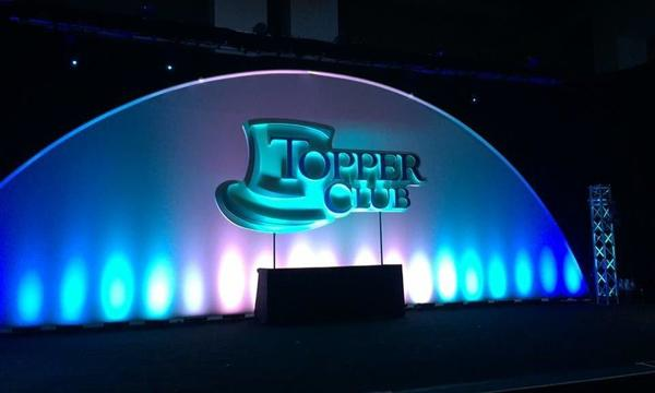 Photo of Topper Club stage with Topper Club logo.