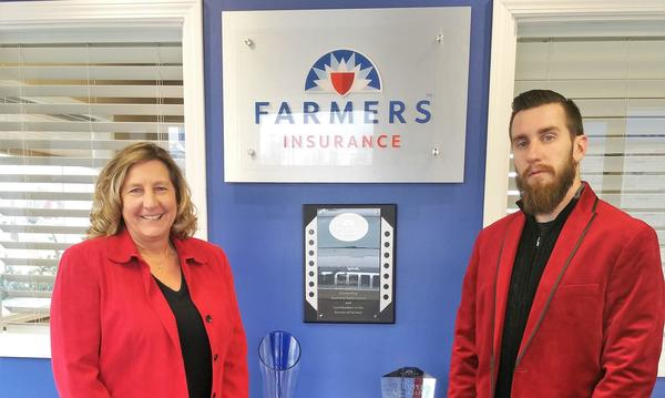 Photo of agent and woman wearing red blazers in front of Farmers logo plaque.