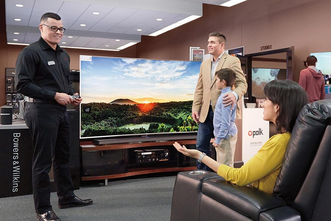 Magnolia Home Theater Certified Consultant helping a family shop for a TV.