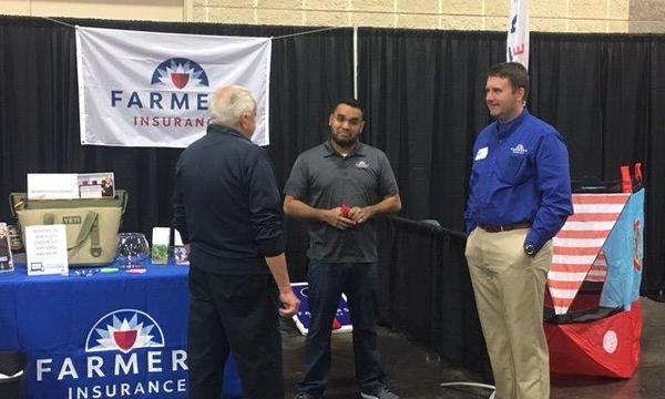 Agent and staff member speaking with a man in front of a Farmers booth
