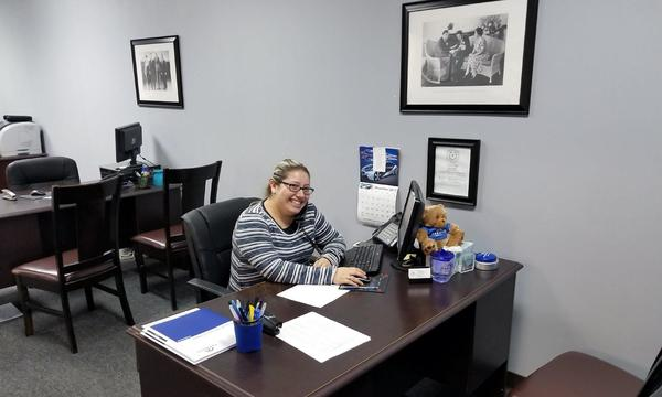 An Arnold Alaniz Agency female staff member sitting behind her desk smiling.