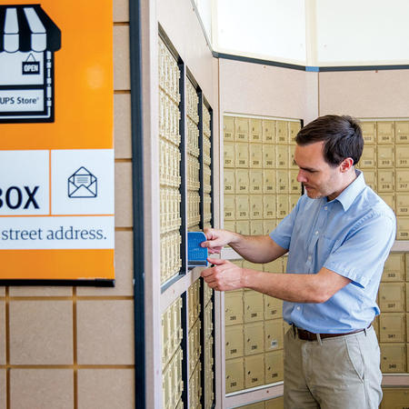 man getting mail from his private mailbox at the ups store