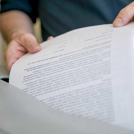 Close up of document being placed in shredding bin