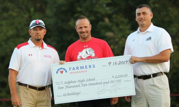 Three men hold an oversized check on a golf course