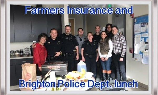 Farmers agents pose with the Brighton Police Department and first responders