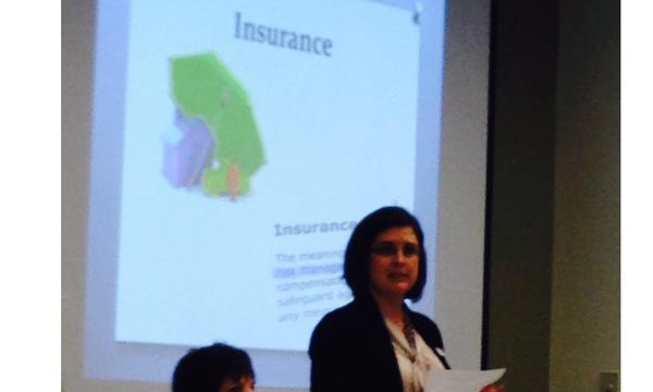 A woman standing in front of a presentation screen that says Insurance on it