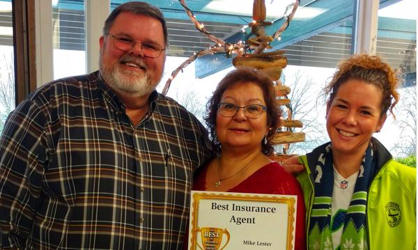 "Farmers agent posing with two women and ""Best Insurance Agent"" certificate"