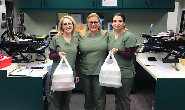 3 nurses holding bags of food