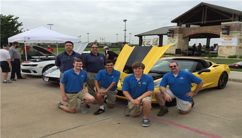 6 male staff members posing by a yellow car