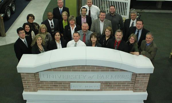 A group of agents standing behind the Farmers University sign.