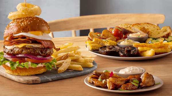 Two gourmet burgers made with a sesame-topped brioche bun and packed with fresh ingredients, served with chips.