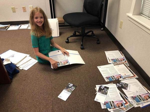 child on the floor organizing paperwork
