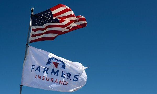 American flag flying above a Farmers Insurance flag