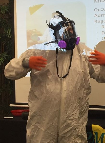 Agent giving educational demonstration - wearing full hazmat suit and face protection.