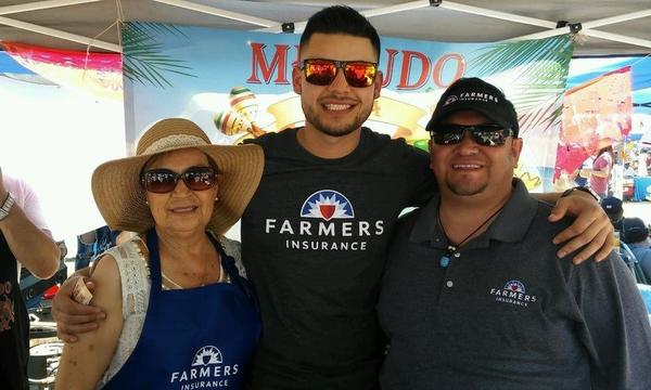 Agent Jose with a woman and a man all wearing Farmers shirts at an event.
