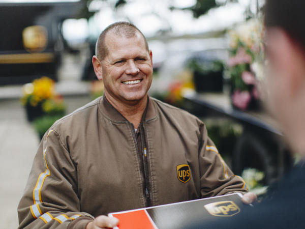 Ups Delivery Man Smiling While Handing Customer Package