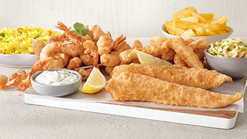 Two fried hake, scampi, calamarie, rice, coleslaw and chips arranged on a grey table.