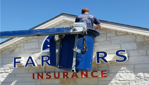Photo of a man installing a Farmers sign on a building.
