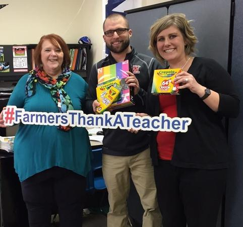 "three adults holding a ""#farmersthankateacher"" sign"