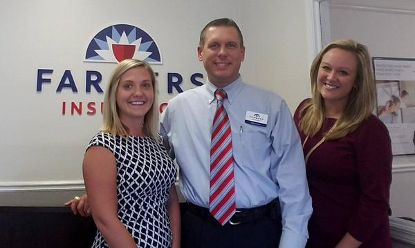A man and two women in professional attire, standing in an office, right in front of a Farmers Insurance sign.