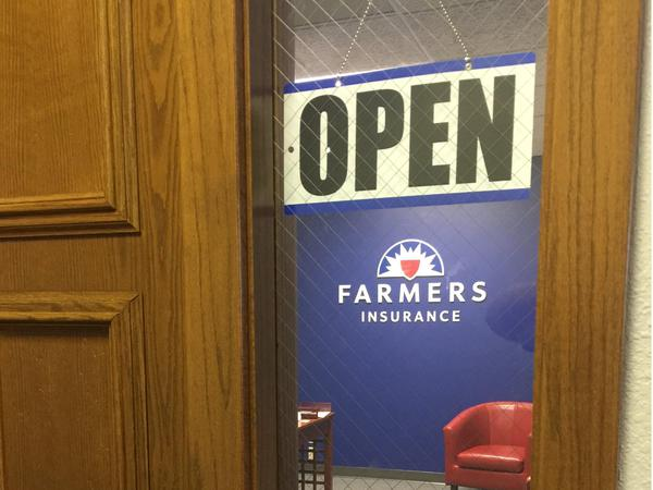 Farmers Insurance wall sign visible through window of office suite