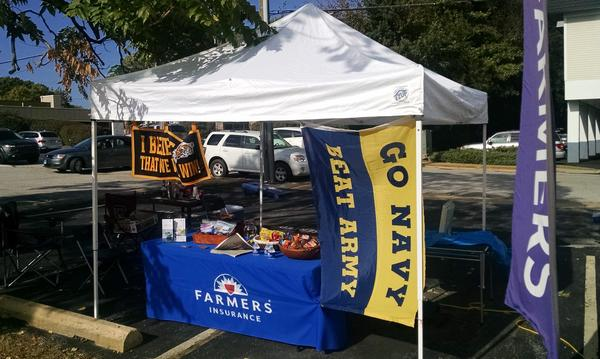 "A Farmers booth outside with a ""Go Navy"" banner"
