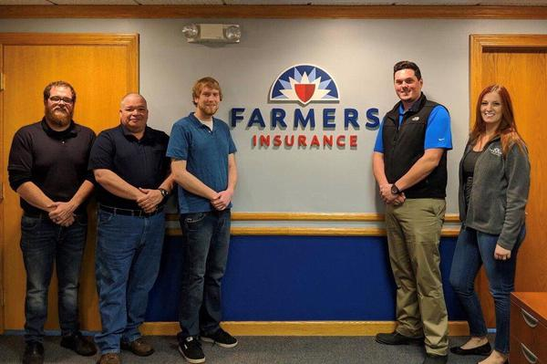 Five people standing in front of Farmers sign