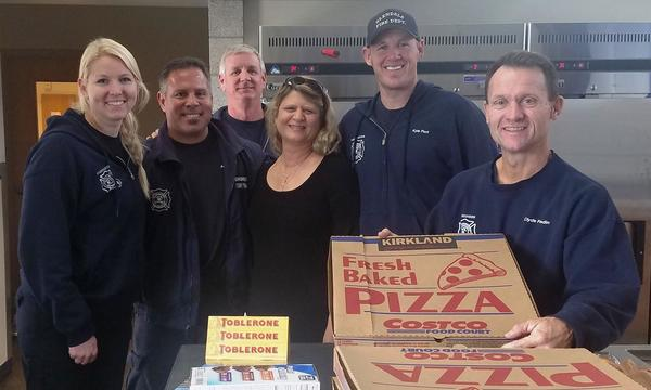 Agent standing with 5 fireman holding up a box of pizza