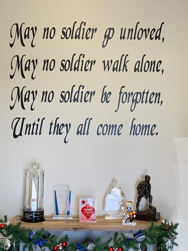 A poem on a wall over a shelf with awards and statues displayed on it