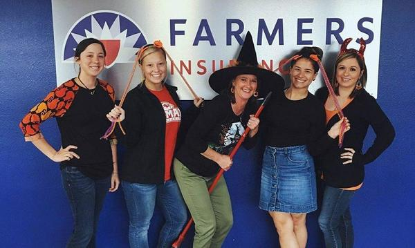 5 female staff member celebrating halloween with funky props.