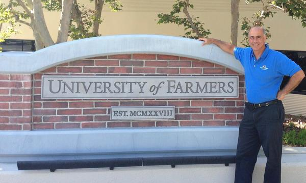 Agent Jose posing next to the University of Farmers brick sign.