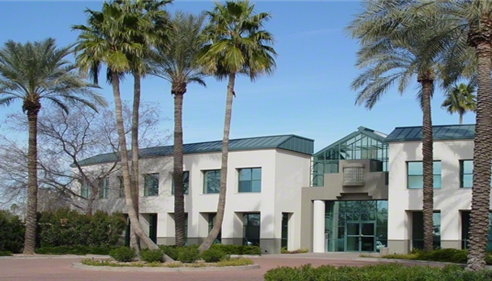 A group of palm trees standing in front of an office complex
