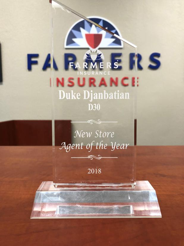 Award on top of desk in front of Farmers Logo