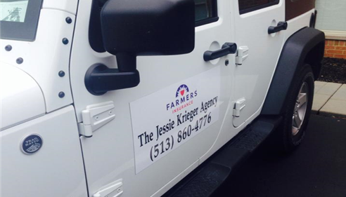 A white Jeep with a decal on the side promoting the agency