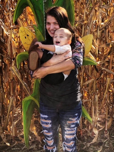 Person holing a baby in front of corn stalks