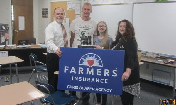 Three adults and a child posing with a Farmers sign.