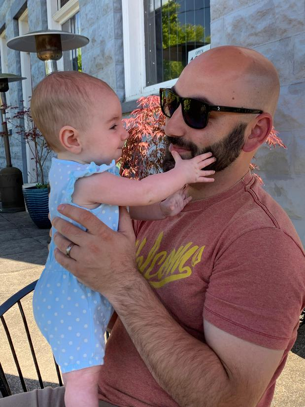 Man in sunglasses holding a baby