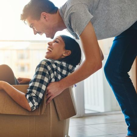Young man pushes young woman in a cardboard box while moving into a new home.