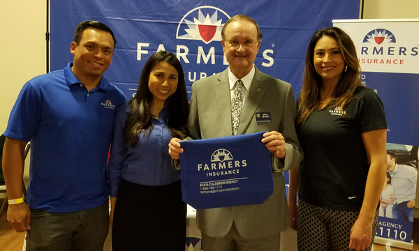 Group of people posing with a Farmers branded towel in front of a Farmers Insurance booth