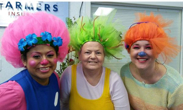 3 women are dressed up in colorful wigs and costumes