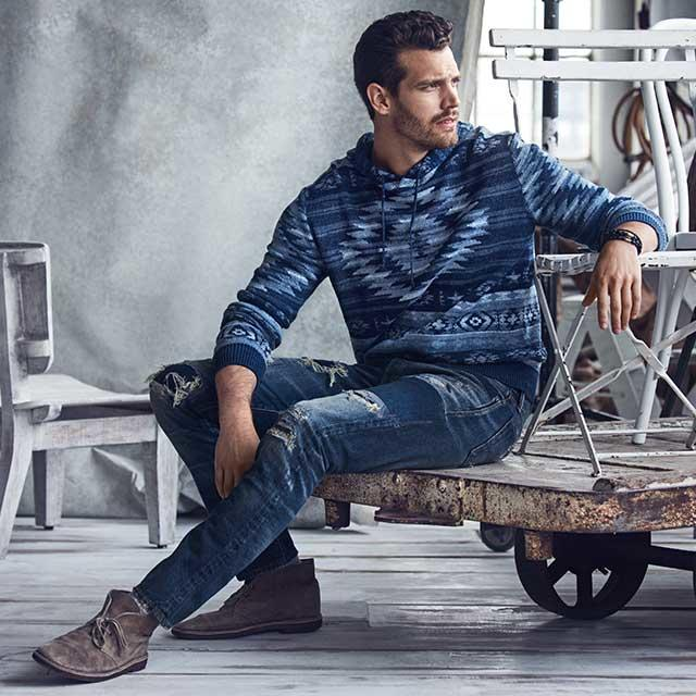 Man in denim pants and a blue sweater sitting on a wooden cart.