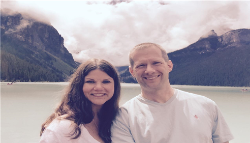 Agent Matt Smith and his wife on vacation in Banff, with a scenic view of a lake and mountains in the background.