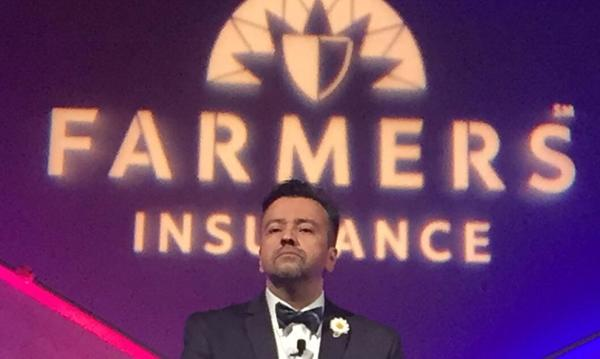 A man in a tuxedo in front of a Farmers logo.