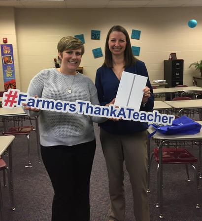 "two adults holding a ""#farmersthankateacher"" sign"