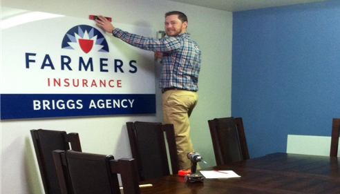 A man hangs up a Farmers Insurance sign in an office