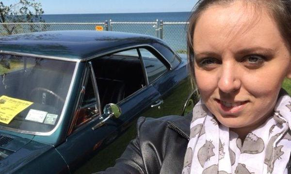 The agent poses for a selfie in front of  a classic car
