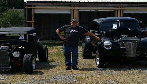 man in between to black classic cars.